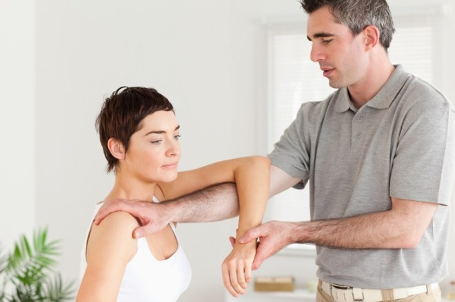 Chiropractor stretching a woman's arm in a room
