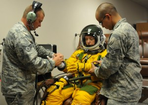 Senior Airmen Kyle Lang (right) and Aaron Saenz (left), 9th Physiological Support Squadron launch and recovery technicians, help Secretary of the Air Force Deborah Lee James properly dress in a high-altitude pressure suit at Beale Air Force Base, California, Aug. 11, 2015.  (U.S. Air Force photo by Senior Airman Dana J. Cable)