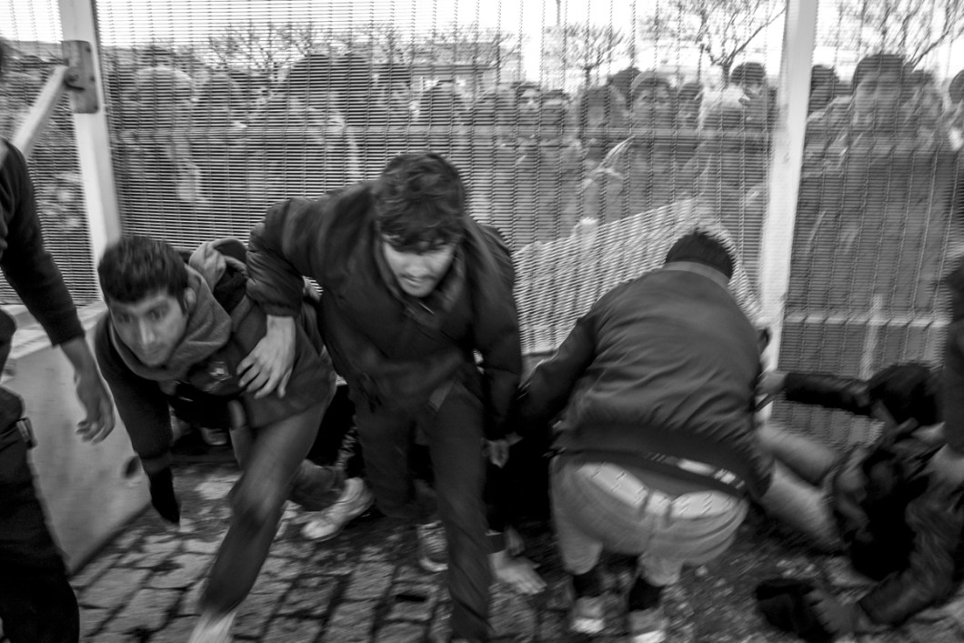 January, 23, 2016 : Tens of refugees passing through the fence of Calais harbour. Two access were open by migrants in differents parts of the fence and around 200 hundred of them succeed to get access to a ferry. Calais, (62), France.