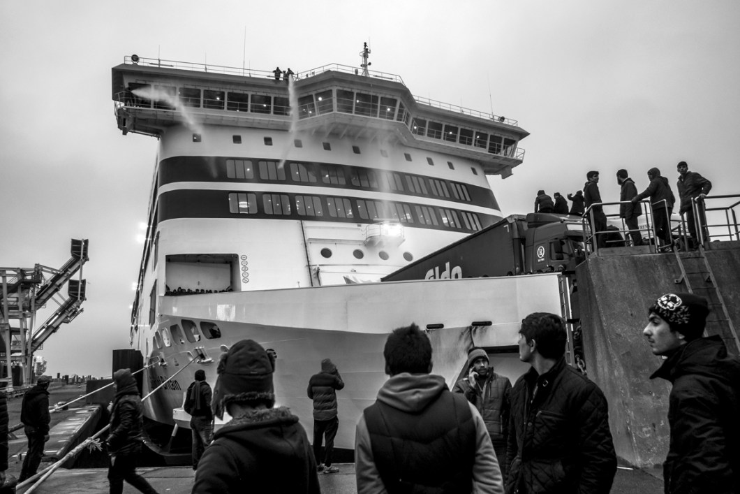 January, 23, 2016 : After thirty minutes refugees start to get out of the boat who was actually arriving from UK. THe personnal of the boat uses water cannons to remove the refugees from the boat. Calais, (62), France.
