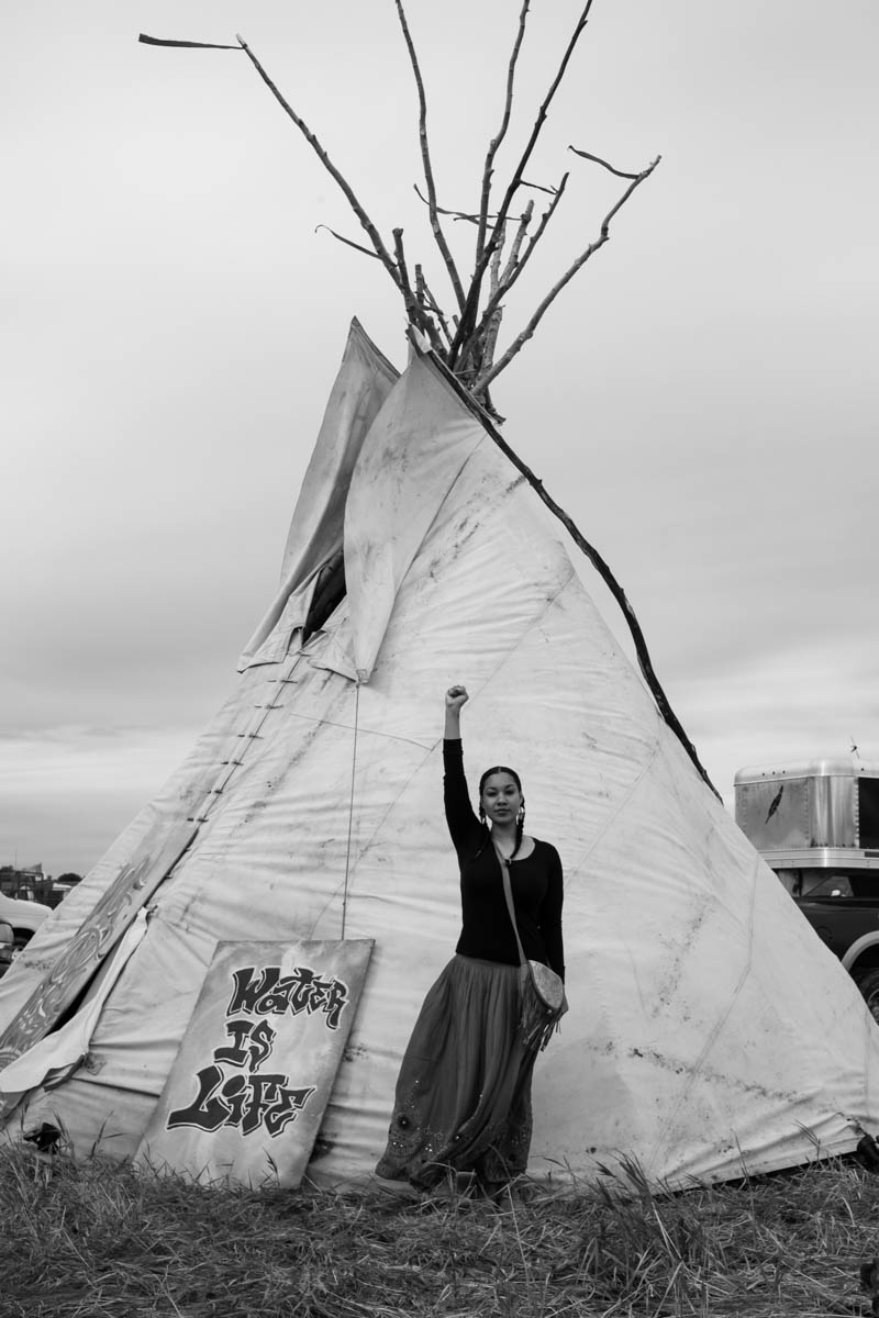 Leah, a water protector in front of her teepee