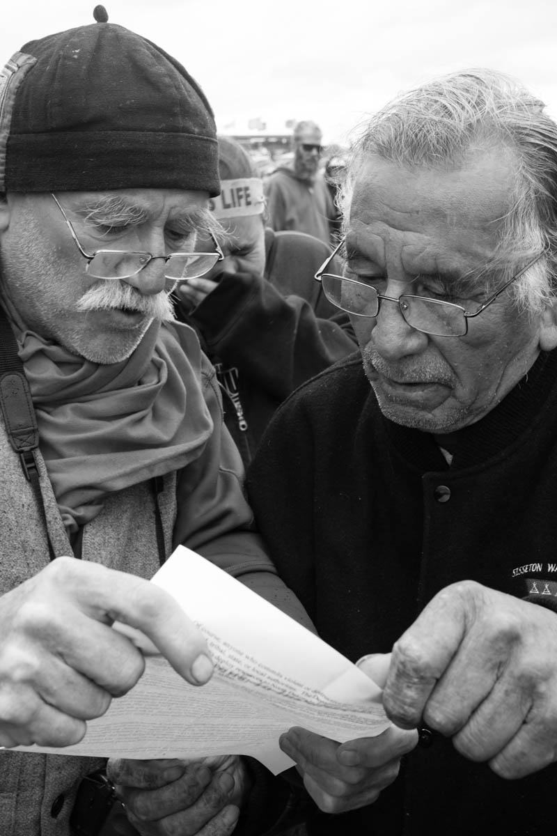 Two men reading a handout of the Department of Justice's decision to put a temporary hold on the construction while a young woman listening them in tears of joy