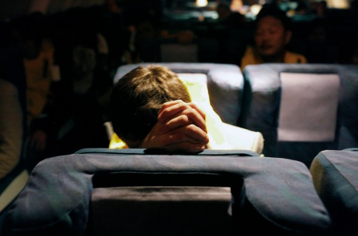 A passenger prays at his seat before landing at Changi Airport in Singapore