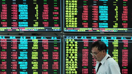 An investor observes stock market at a stock exchange hall in Jiujiang, China.