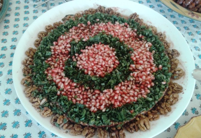 Muhammara decorated with pomegranate seeds, chopped green onions ans walnut