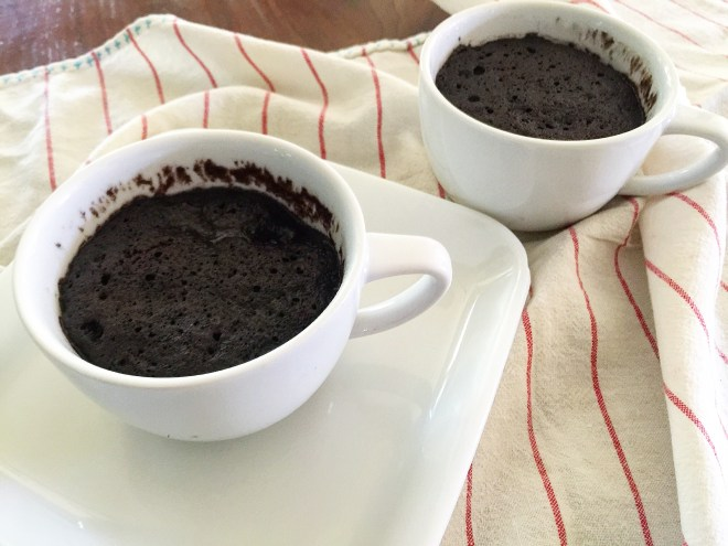 two baked chocolate mug cakes on a countertop