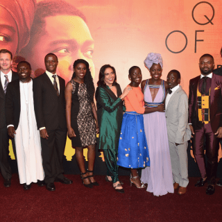 "HOLLYWOOD, CA - SEPTEMBER 20: (L-R) Actors David Oyelowo, Lupita Nyong'o and Madina Nalwanga, chaperone Mark Mugwana, Executive Vice President of Production, The Walt Disney Studios, Tendo Nagenda, President of Walt Disney Studios Motion Picture Production, Sean Bailey, Chess Coach and Director of Sports Outreach in Uganda, Robert Katende, Ugandan national chess champion Phiona Mutesi, Director Mira Nair, actor Martin Kabanza and composer Alex Heffes arrive at the U.S. premiere of Disney's ""Queen of Katwe"" at the El Capitan Theatre in Hollywood. The film, starring David Oyelowo, Oscar winner Lupita Nyong'o and newcomer Madina Nalwanga, is directed by Mira Nair and opens in U.S. theaters in limited release on September 23, expanding wide September 30, 2016. On September 20, 2016 in Hollywood, California. (Photo by Alberto E. Rodriguez/Getty Images for Disney)"