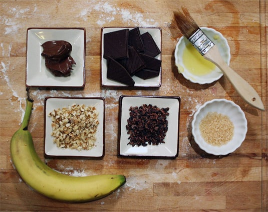 A selection of toppings for sweet mini-pizzas: Nutella, dark chocolate, butter, sugar, cocoa nibs, chopped walnuts and banana.