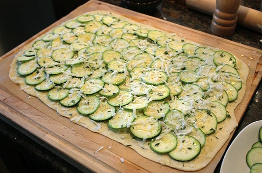 Sprinkle zucchini with a generous pinch of fleur de sel (make sure the salt is distributed evenly all over the pizza), then with ground black pepper, thyme and the remaining parmigiano-reggiano. Drizzle with remaining garlic-infused extra-virgin olive oil.