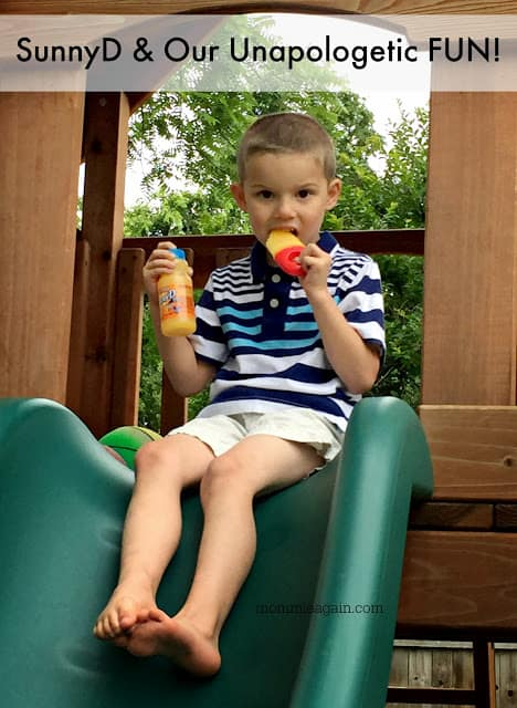 Boy child playing on playset outside while drinking SunnyD