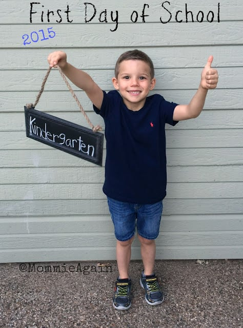 5 year old boy holding up a kindergarten sign and one thumb up