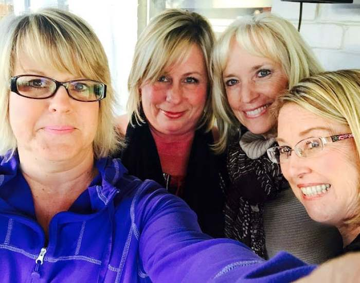 Four ladies over 50 with blonde hair taking a group picture
