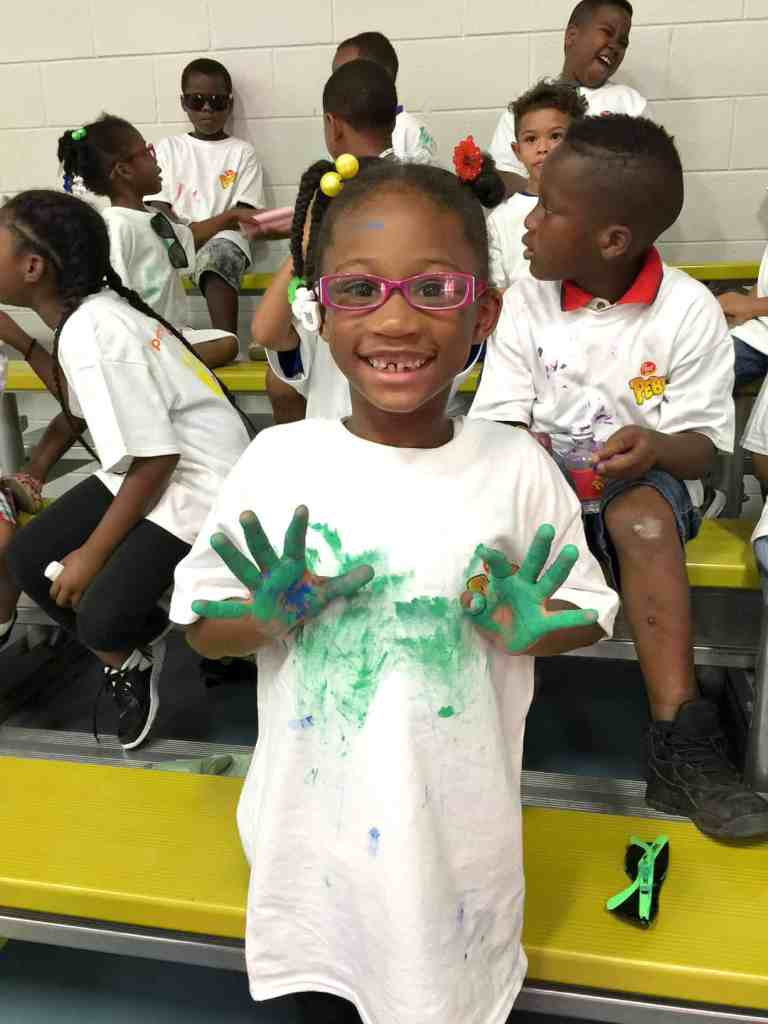 little girl gets paint on hands while painting mural at BGCD Oak Cliff