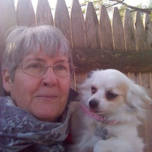 Mary Callahan head shot in front of wood fence, holding her small white dog
