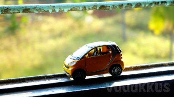 A Toy SMART Car on a Train Window Sill (Macro Photography)