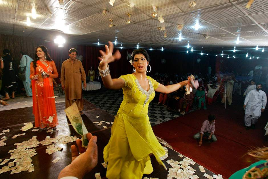 A man offers money to Sonia, 26, a transgender Pakistani, while dancing at a birthday party in Rawalpindi, Pakistan. (AP Photo/Anjum Naveed)