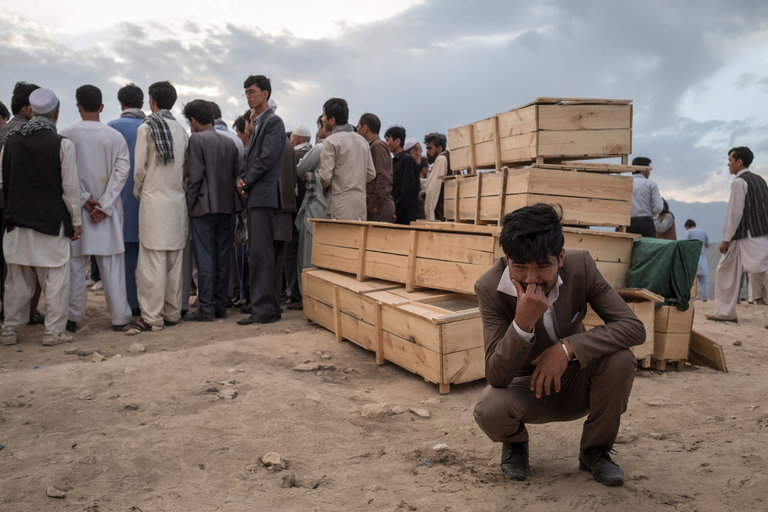 ethnic Hazara man cries next to empty caskets on Sunday during burial ceremonies at a cemetery in the Omid-e-Sabz Township near Kabul, Afghanistan. Credit Adam Ferguson for The New York Times