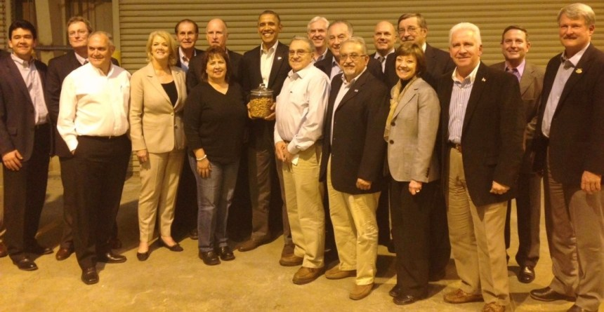 President Barack Obama (holding a jar of nuts that had been presented) is surrounded by those who were invited to attend a town hall type session on California's drought at a San Luis Water District facility in western Merced County. The Friant Water Authority was represented by General Manager Ronald D. Jacobsma (back row, fourth from right) and Assistant General Manager Mario Santoyo (front row, third from right).