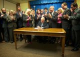 Governor Jerry Brown signs the bill placing the water bond, Proposition 1, on the November ballot with Republican and Democratic legislators applauding.