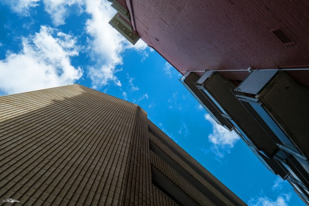 Two buildings photographed against a blue sky