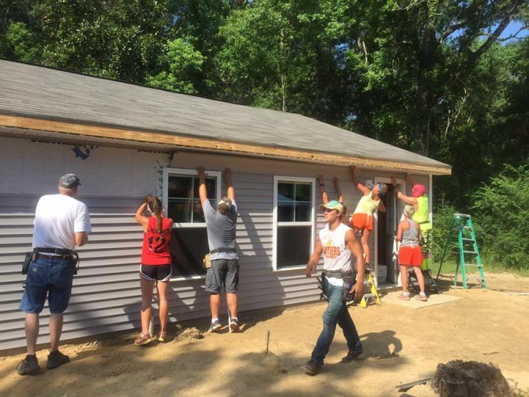 Volunteers work Thursday on siding.