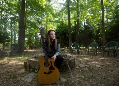 "Smithfield's Bria Kelly, 18, sits with her guitar in her backyard on Wednesday afternoon. Kelly made it to the final 10 contestants on NBC's ""The Voice"" out of 70,000 people who initially auditioned this season."