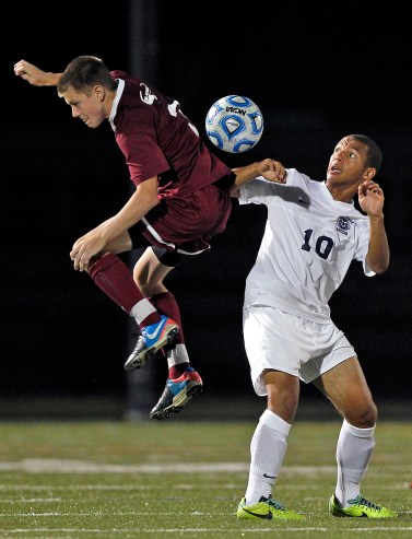 Lafayette's Denzel Spped, right, looks for the ball as Poquoson's Dylan Paul, left, jumps during Tuesday's Conference 25 soccer semifinals at Wanner Stadium. (Photo by Jonathon Gruenke)