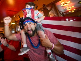 Emmanuel Zapata celebrates with son Alex Zapata, 3, while watching the second half of the United States' World Cup match against Ghana at Park Lane Tavern in Hampton on Monday.