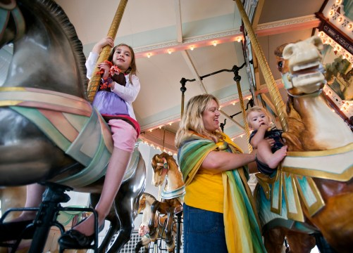 Stacey Griffin, center, and children Katherine, 8, and Nathan, 1, enjoy a ride on the Hampton Carousel on Monday afternoon. (Photo by Kaitlin McKeown)