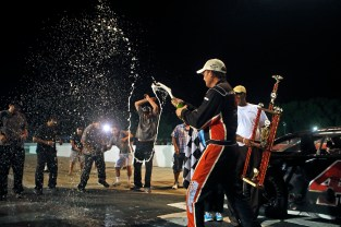 C.E. Falk III celebrates by throwing champagne at his crew members after winning Saturday's Hampton Heat 200 at Langley Speedway. (Photo by Jonathon Gruenke)