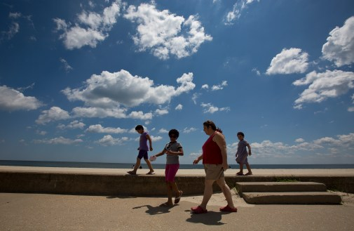 Christine Hadley walks on the boardwalk at Buckroe Beach with her three daughters, from left, Bella, 7, Catherine, 10, and Diana, 5, on Monday. As a part of an action plan developed during a diabetes self-management class, Hadley walks on the beach several times a week to maintain her fitness.