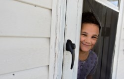 Diana Hadley, 5, peeks through the screen of her front door in Hampton on Monday.