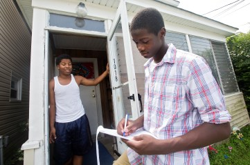 Malik Spencer, 15, right, surveys Andre Payne, 19, as a part of the Newport News Department of Human Services TOP Program on Monday in Southeast Newport News. The program, part of a larger grant-based initiative to prevent youth violence, offers a stipend to youth to go out into their neighborhoods, survey residents and coordinate meetings to discuss issues of community interest. (Photo by Kaitlin McKeown)