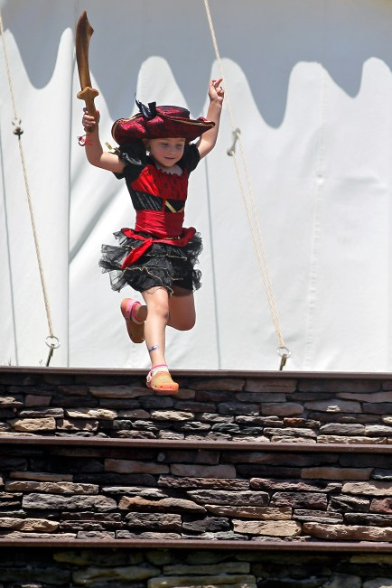 Kamryn Kershaw, 5, leaps down steps while holding a sword during Saturday's Blackbeard Pirate Festival in Hampton.