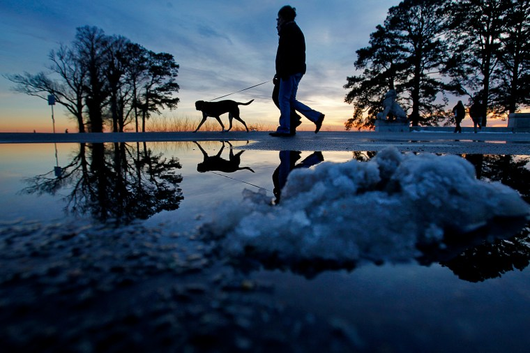 Patrik and Camilla Lasson walk their dog Roxy as snow piles melt while the sun sets Friday evening near Lions Bridge. (Photo by Jonathon Gruenke/Daily Press)