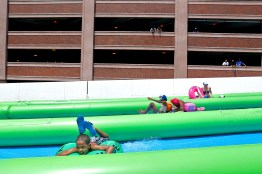 Guests slide down in tubes down Settlers Landing Road during Saturday's Slide the City event in Hampton. The water slide stretched from Settlers Landing Bridge to the front of the Crown Plaza Hotel.