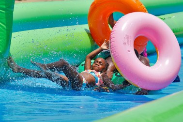Ayanna Brown, 6, loses control of her tube while sliding down Settlers Landing Road during Saturday's Slide the City event in Hampton. The water slide stretched from Settlers Landing Bridge to the front of the Crown Plaza Hotel.