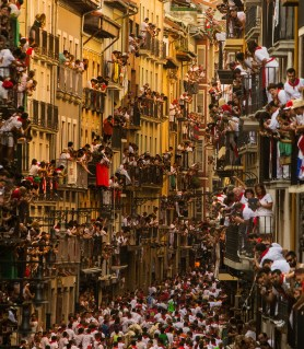 People watch as Jandilla fighting bulls and revelers run during the running of the bulls, at the San Fermin festival, in Pamplona, Spain, Tuesday, July 7, 2015. (AP Photo/Andres Kudacki)