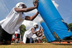 Heritage players practice hitting the sled during the opening day of football practice Thursday afternoon.