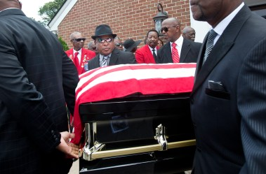 Members of the Tidewater Chapter of Tuskegee Airmen, Inc. watch as pallbearers carry the casket of Tuskegee Airman William R. White on Thursday at Little Zion Baptist Church in Smithfield, Va. (Kaitlin McKeown)