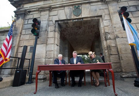 From left, former U.S. Rep. Jim Moran, Gov. Terry McAuliffe and National Park Service Deputy Director Margaret O'Dell sign the deed for the transfer of lands to the National Park Service during a ceremony on Tuesday at Fort Monroe.