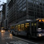 The only lights are those of cars and overcrowded buses