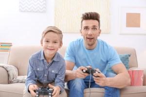 vater und sohn spielen zusammen ein videospiel
