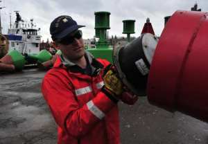 Seaman Zach Beyer, of Coast Guard Buckthorn, removes a battery on a lighted, radar-reflective buoy during routine shoreside maintenance at Coast Guard Sector Sault Ste. Marie. U.S. Coast Guard photo by Petty Officer 1st Class Charles C. Reinhart.