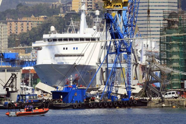 A crane barge is pictured in front of the debris of the collapsed control tower of the port in Genoa May 8, 2013.  Image (c) REUTERS/Alessandro Garofalo