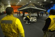 (May 13, 2013) An X-47B Unmanned Combat Air System (UCAS) demonstrator is towed into the hangar bay of the aircraft carrier USS George H.W. Bush (CVN 77).  George H.W. Bush is  the first aircraft carrier to catapult launch an unmanned aircraft from its flight deck.  (U.S. Navy photo by Mass Communication Specialist 2nd Class Timothy Walter/Released)