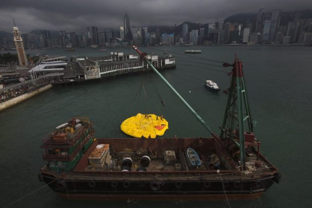 A deflated Rubber Duck by Dutch conceptual artist Florentijn Hofman, is lifted up for repair by a crane on a ship in Hong Kong's Victoria Harbour May 15, 2013. REUTERS/Tyrone Siu