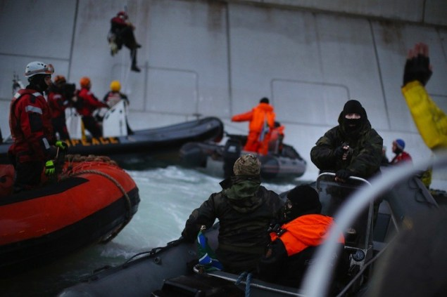 A Russian Coast guard officer is seen pointing a gun at a Greenpeace International activist as five activists attempt to climb the 'Prirazlomnaya,' an oil platform operated by Russian state-owned energy giant Gazprom platform in Russias Pechora Sea.  This is one example of the disproportionate use of force by the Russian authorities during a peaceful protest. The activists are there to stop it from becoming the first to produce oil from the ice-filled waters of the Arctic. Image (c) Greenpeace