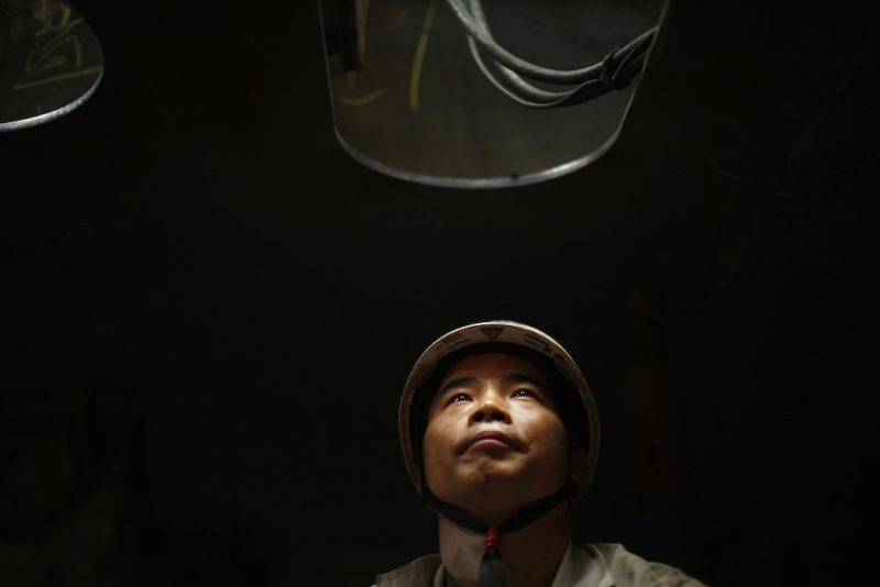 A labourer takes a break as he work inside a ship which is under construction at the Waigaoqiao shipyard in Shanghai November 5, 2013. REUTERS/Carlos Barria