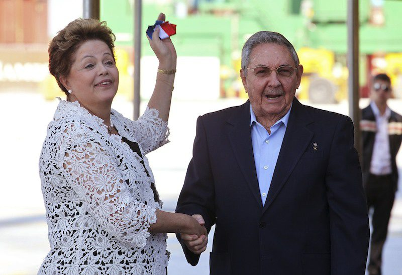 Brazil's President Dilma Rousseff (L) holds a piece of ribbon after she and her Cuban counterpart Raul Castro cut the ribbon in a ceremony attended by other regional leaders in Cuba for a Latin American and Caribbean summit, in Mariel on the outskirts of Havana January 27, 2014. REUTERS/Stringer